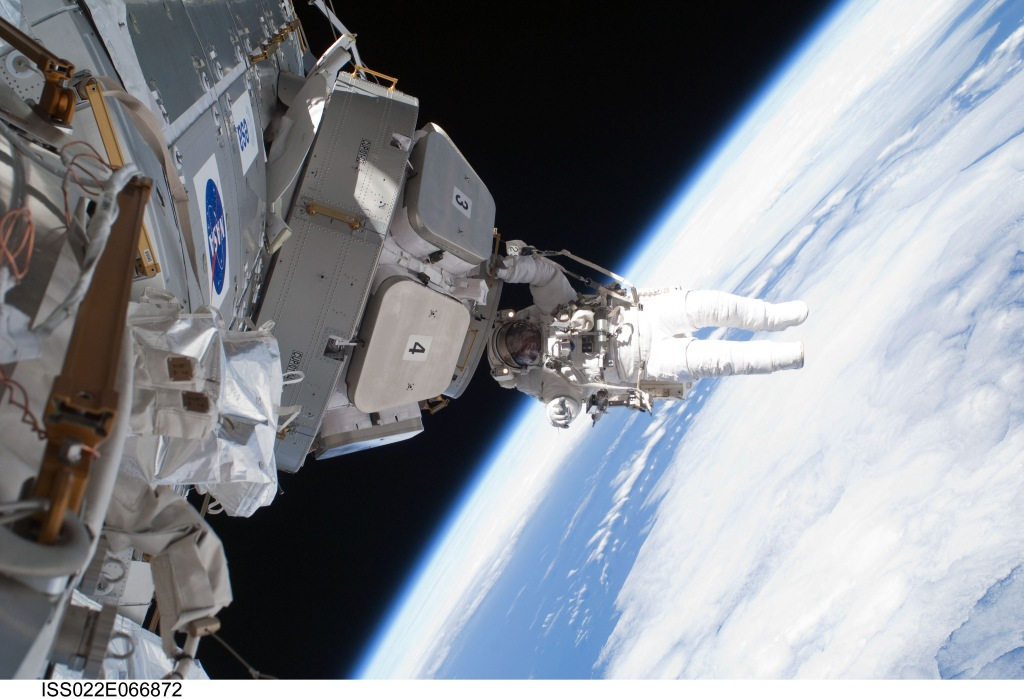 Floating just below the International Space Station, astronaut Nicholas Patrick put some finishing touches on the newly installed cupola space windows last week. Patrick was a mission specialist onboard the recently completed space shuttle Endeavor's STS-130 mission to the ISS. Pictured, Patrick floats near the outermost of seven windows on the new cupola of the just-installed Tranquility module. Patrick hovers about 340 kilometers over the Earth's surface, well in front of the blue sky, blue water, and white clouds pictured far in the background. In the above image, covers on windows three and four were in place and clearly labelled. Images from inside the ISS's new panoramic cupola are now available.